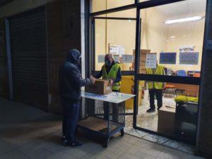 Volontari in azione nella distribuzione di alimenti di prima necessità.